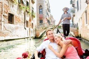 Romantic travel couple in Venice on Gondole ride romance in boat
