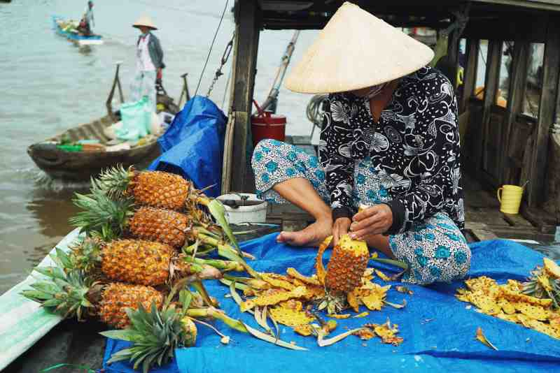 pineapple being cut in a boat - vietnam